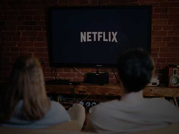 Couple Streaming Netflix on Couch